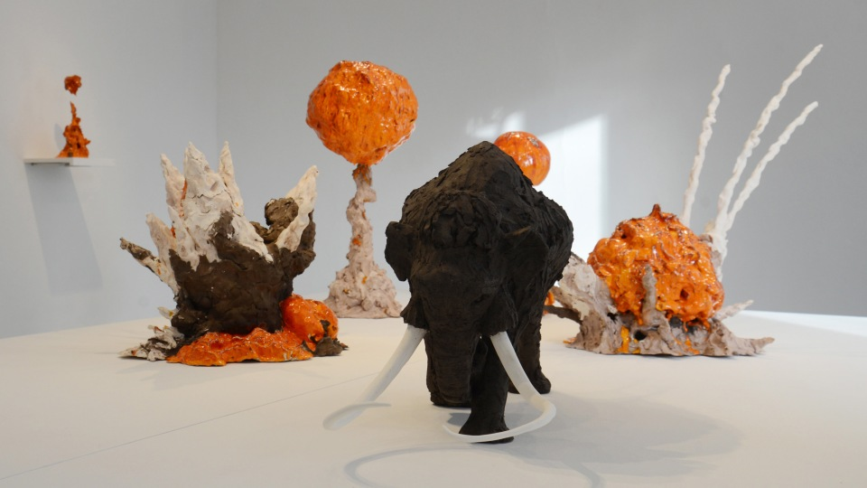 EXPLO!/EXTINCT!. Skulpterad mammut omgiven av orangea skulpterade explosioner